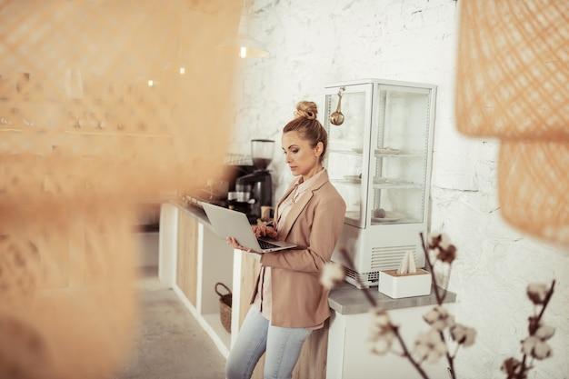 Altijd aan het werk. mooie geconcentreerde vrouw die bij de salontafel staat en op haar laptop werkt.