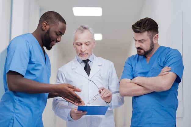Altijd blij om meningen te delen. gemakkelijke bebaarde verouderende arts die in het ziekenhuis staat terwijl hij de map vasthoudt en een gesprek voert met jonge collega's