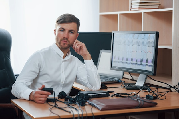 Altijd blij om u te helpen. polygraaf-examinator werkt op kantoor met de apparatuur van zijn leugendetector