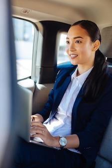 Altijd druk. aangename zelfverzekerde zakenvrouw die op haar laptop werkt terwijl ze in de auto zit
