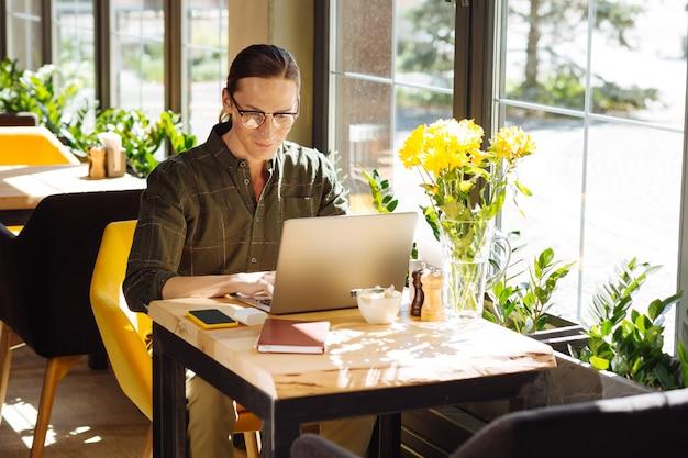 Altijd druk. knappe langharige man die zich op zijn werk concentreert terwijl hij met zijn laptop in het café zit