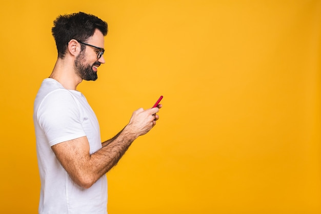 Altijd in contact. gelukkig jonge man in glazen typen sms geïsoleerd op gele achtergrond, glimlachend en camera kijken.