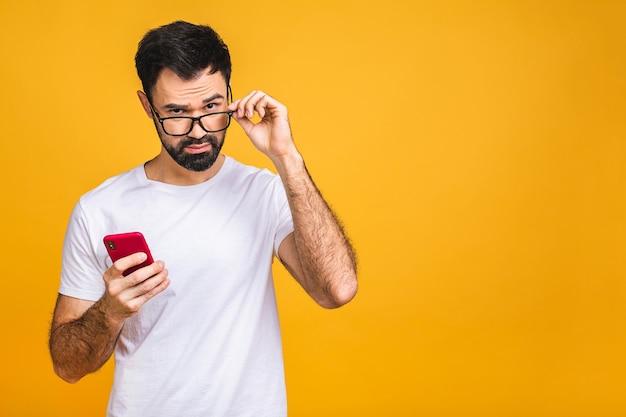 Altijd in contact. gelukkig jonge verbaasd geschokt bebaarde man in glazen sms typen op gele achtergrond.