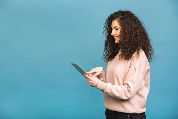 Altijd in contact! mooi krullend jong meisje glimlachend met behulp van tablet geïsoleerd op blauwe achtergrond. kopieer ruimte voor tekst.