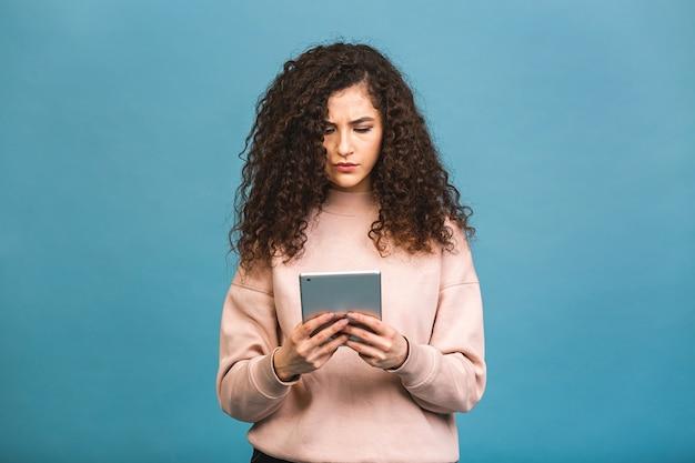 Altijd in contact! mooi krullend jong meisje glimlachend met behulp van tablet geïsoleerd op blauwe achtergrond.
