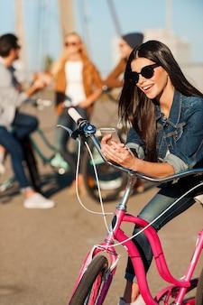 Altijd in contact. mooie jonge glimlachende vrouw die op haar fiets leunt en naar haar mobiele telefoon kijkt terwijl haar vrienden op de achtergrond praten