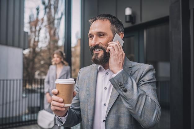 Altijd in contact. volwassen gelukkig bebaarde man in pak met smartphone in de buurt van oor koffie drinken in straat en vrouw op afstand