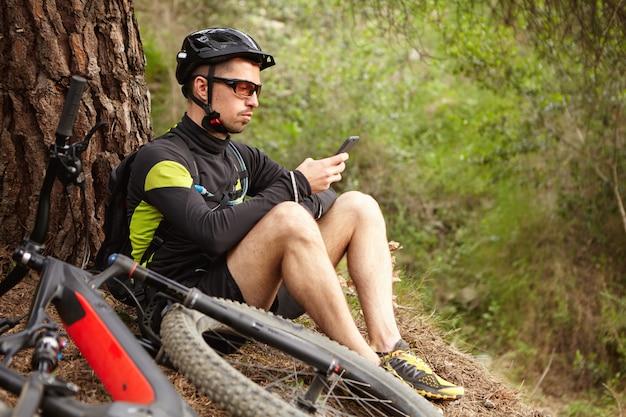 Altijd in contact. zelfverzekerde mannelijke fietser die bericht typt of naar gps-coördinaten zoekt op smartphone, zittend op gras onder grote boom terwijl het fietsen in bos, zijn e-fiets die op grond naast hem ligt