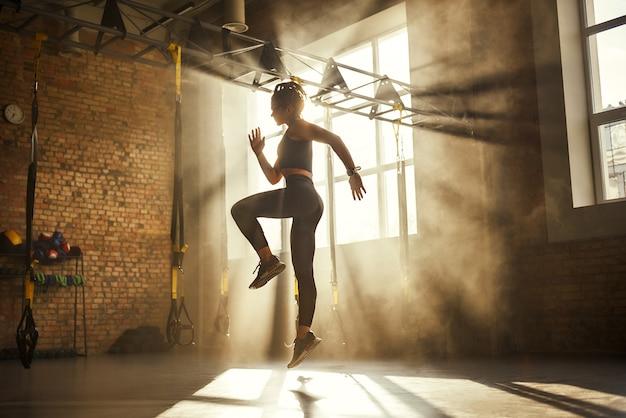 Altijd in goede vorm, volledige lengte van atletische vrouw in zwarte sportkleding die traint in