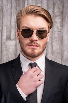 Altijd in stijl. knappe jonge man in formalwear die zijn stropdas aanpast en één hand in de zak houdt