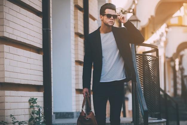 Altijd in stijl. knappe jonge man in slimme vrijetijdskleding draagtas en het aanpassen van zijn zonnebril terwijl hij op straat staat