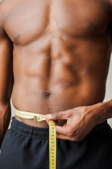 Altijd in vorm. bijgesneden afbeelding van gespierde zwarte man die zijn taille meet met meetlint