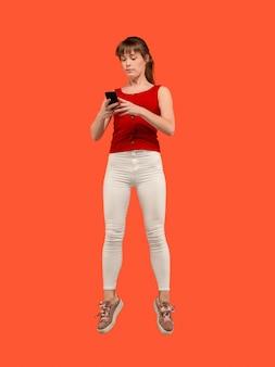 Altijd mobiel. volledige lengte van vrij jonge vrouw die telefoon neemt terwijl het springen tegen rode studioachtergrond. mobiel, beweging, beweging, bedrijfsconcepten