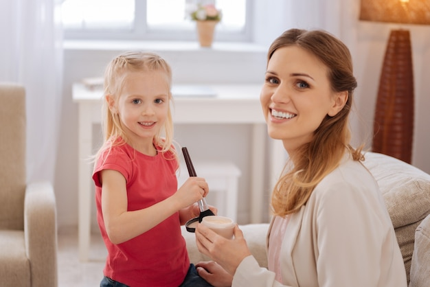 Altijd mooi. leuke vrolijke positieve moeder en dochter die en u glimlachen terwijl zij een make-uples hebben