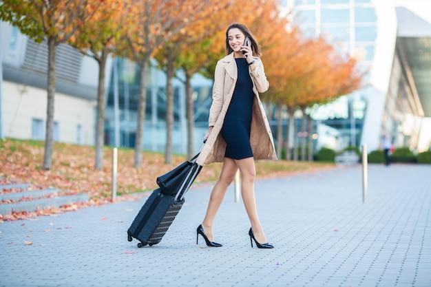 Altijd onderweg. vrouw die in luchthaven en bespreking bij mobiele telefoon loopt