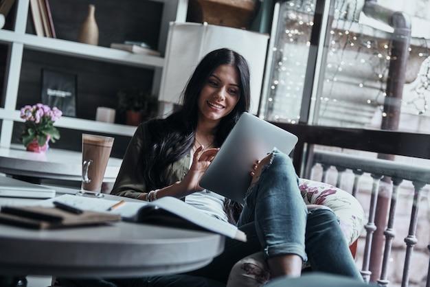 Altijd online. aantrekkelijke jonge lachende vrouw met behulp van digitale tablet