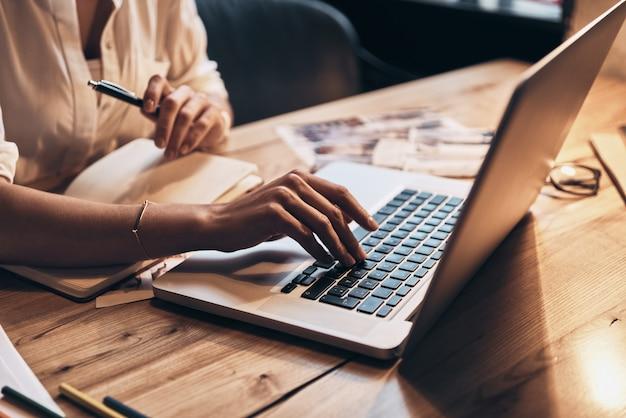 Altijd online. close-up van een jonge vrouw die aan het werk is met een computer terwijl ze in haar werkplaats zit