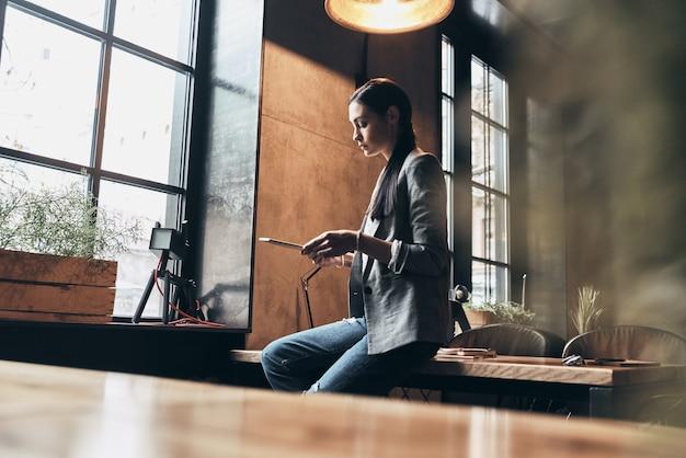Altijd online. ernstige jonge vrouw in slimme vrijetijdskleding die digitale tablet gebruikt terwijl ze op het bureau leunt