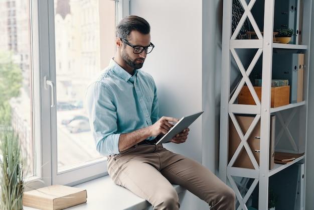 Altijd online. jonge moderne zakenman die digitale tablet gebruikt terwijl hij op de vensterbank op kantoor zit