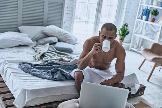 Altijd online. knappe jonge afrikaanse man bedekt met een douchehanddoek die koffie drinkt