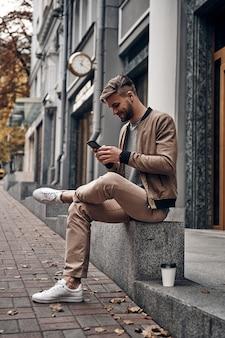 Altijd online. knappe jonge man in vrijetijdskleding die zijn smartphone gebruikt terwijl hij buiten zit