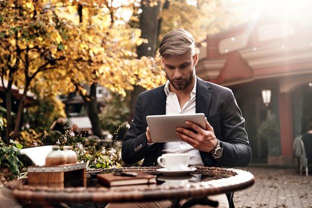 Altijd online. knappe jongeman in slimme vrijetijdskleding met behulp van digitale tablet terwijl hij buiten in restaurant zit
