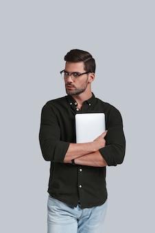 Altijd online. knappe jongeman met een bril die zijn digitale tablet vasthoudt en wegkijkt terwijl hij tegen een grijze achtergrond staat