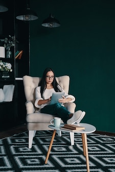 Altijd online. mooie jonge vrouw die digitale tablet gebruikt terwijl ze in de fauteuil zit