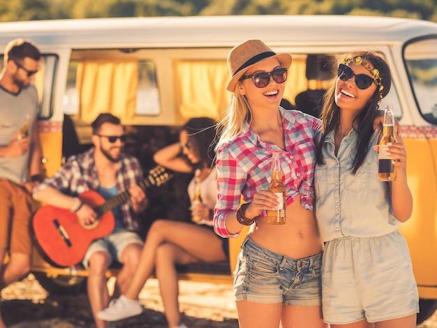 Altijd samen en nooit apart. twee vrolijke jonge vrouwen die flessen bier vasthouden terwijl hun vrienden op de achtergrond zitten in een retro minibusje