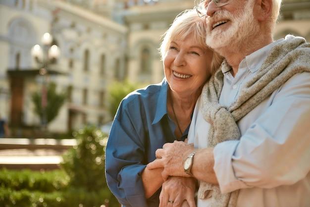 Altijd samen gelukkig senior koppel dat aan elkaar hecht en glimlacht terwijl ze samen tijd doorbrengen