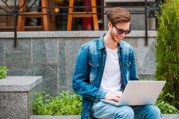 Altijd verbonden. glimlachende jonge man die op laptop werkt terwijl hij buiten zit