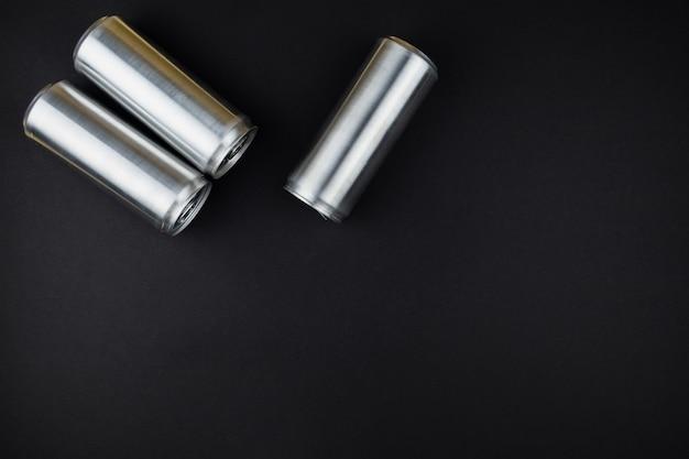 Aluminium blikjes staan achter elkaar op een zwart bureau