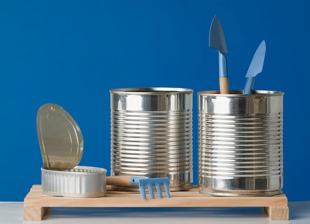Aluminium kanonnen gebruikt als containers voor het kweken van planten op blauwe achtergrond