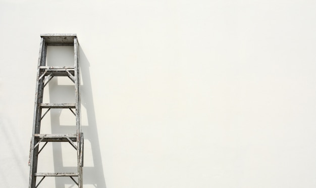 Aluminium opvouwbare ladder en de schaduw op witte cementmuur