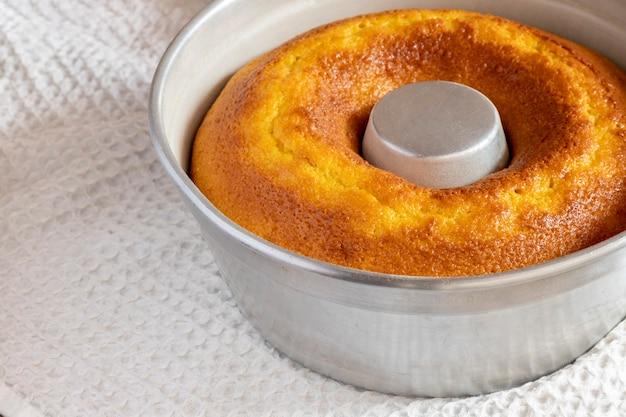 Aluminium pan met maïsmeelcake om uit de vorm te halen