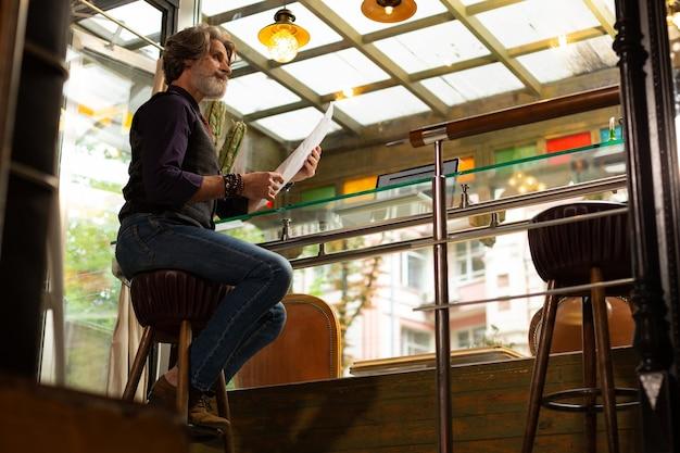 Alvorens te bestellen. nadenkende man zit op een barkruk met een menu in zijn handen en denkt eraan iets nieuws te proberen in een coffeeshop.