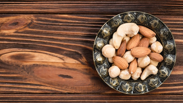 Amandel; cashewnoten en hazelnoten in antieke metalen kom op houten bureau