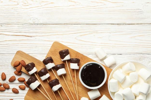 Amandel en marshmallow in chocolade op witte houten achtergrond, bovenaanzicht