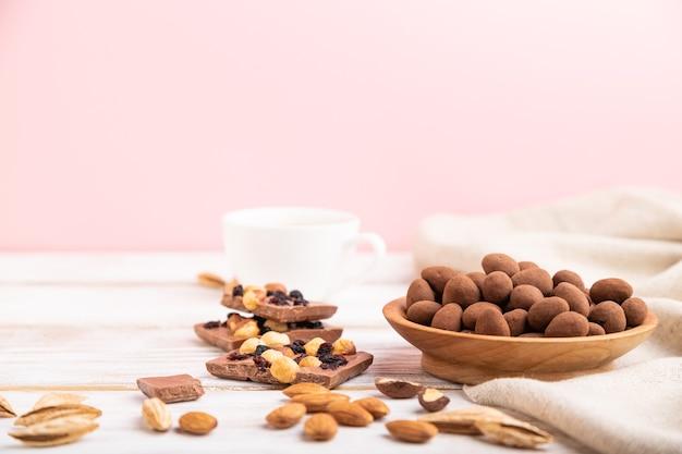 Amandel in chocolade dragees in houten plaat en een kopje koffie op witte en roze achtergrond en linnen textiel. zijaanzicht, kopie ruimte, selectieve aandacht.