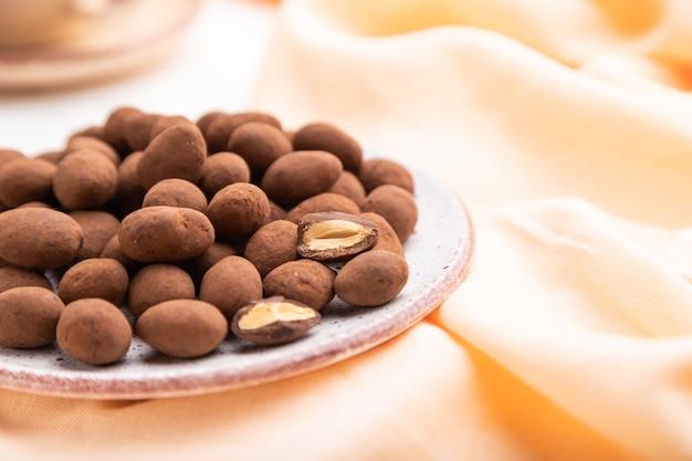 Amandel in chocolade dragees op keramische plaat en een kopje koffie op witte betonnen achtergrond en oranje linnen textiel. zijaanzicht, close-up, selectieve aandacht.