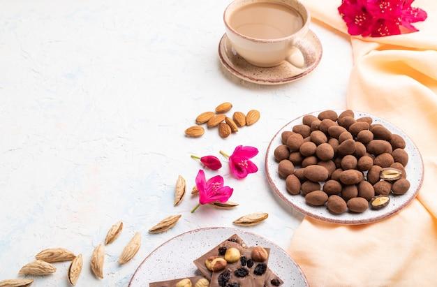 Amandel in chocolade dragees op keramische plaat en een kopje koffie op witte betonnen achtergrond en oranje linnen textiel. zijaanzicht, kopieer ruimte.