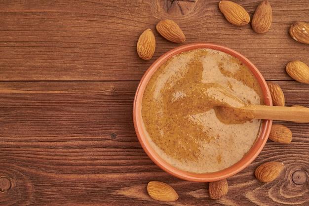 Amandelboter, rauwe voedselpasta gemaakt van vermalen amandelen in notenboter, knapperig en roer
