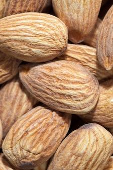 Amandelen die worden gebruikt voor voedsel en voor het koken van verschillende gerechten, harde rauwe kant-en-klare amandelen, goudkleurige noten nuttig en rijk aan eiwitten en mineralen amandelen