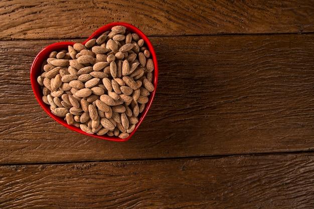 Amandelen in een hartpot op houten achtergrond