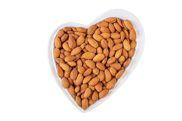 Amandelen in hartvormige plaat geïsoleerd op wit vegetarische snacks.