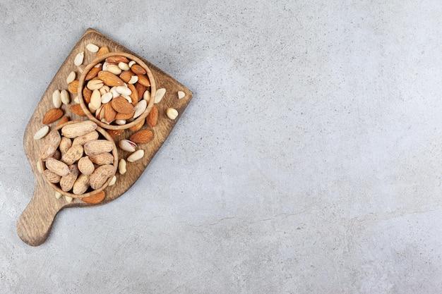Amandelen, pistachenoten en pinda's opgestapeld in en rond houten kommen op een houten bord op marmeren ondergrond
