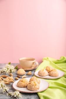 Amandelkoekjes en een kopje koffie op een grijs en roze ondergrond en groen linnen textiel