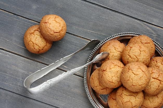 Amandelkoekjes met suikertang op rustieke houten lijst