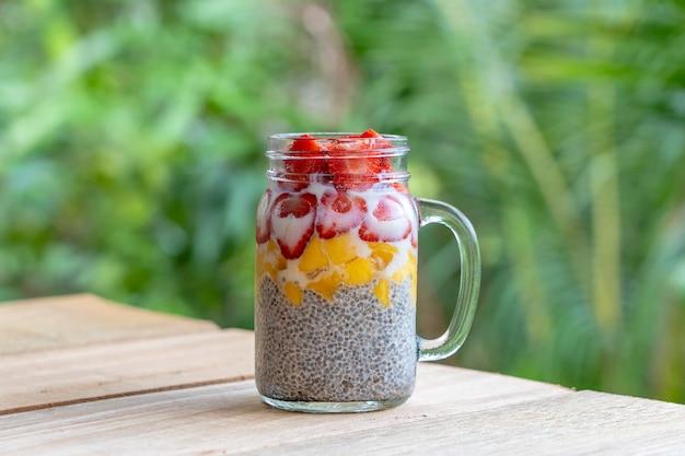 Amandelmelk chia pudding met verse aardbeien en mango in een glazen pot mok.
