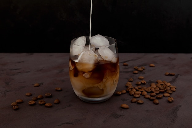 Amandelmelk die in ijskoffie op een bruine lijst wordt gegoten